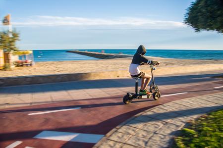 Guy gekleed in kiel met capuchon paardrijden elektrische scooter langs herfst strand. Avond. Horizontaal.