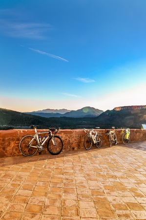 parked bikes: Beautiful mountain scene in last rays of setting sun and four sport bikes parked on the observation platform. Healthy lifestyle concept. Vertical. Stock Photo