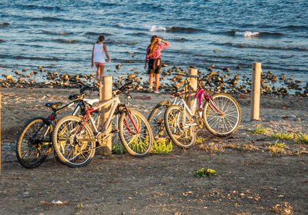 parked bikes: Evening beach, parked bikes, two girls on background of blue sea. Healthy lifestyle concept. Horizontal. Stock Photo