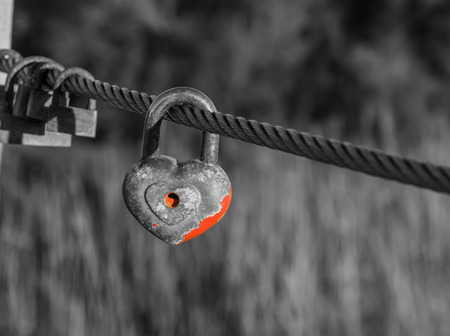Heart shaped padlock with peeled off red paint in enlarged view and other old rusty padlocks as symbol of eternal love hanging on metal cable in black and white composition. Romance concept. Blurred background. Stock Photo
