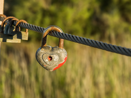 Heart shaped padlock with peeled off red paint in enlarged view and other old rusty padlocks as symbol of eternal love hanging on metal cable. Romance concept. Natural blurred background. Stock Photo