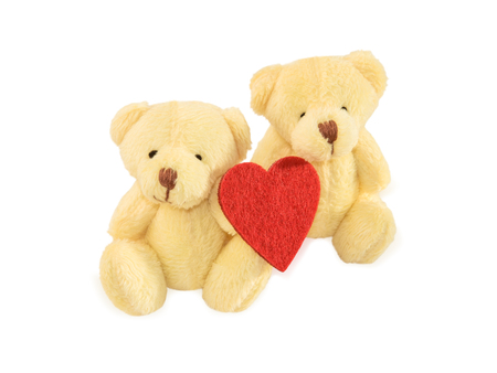 Two teddy bears sitting with red felt heart isolated over white. Valentines Day and love concept. Stock Photo