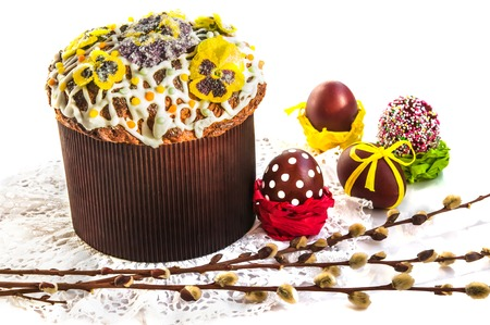 Easter composition: typical cake covered with icing, sprinkled with color pops and candied flowers, pasch eggs and willow branches on lace napkin. Selective focus, white background, copy space. Stock Photo