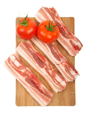 Raw red meat fat bacon and tomato on a wooden board isolation on white. photo
