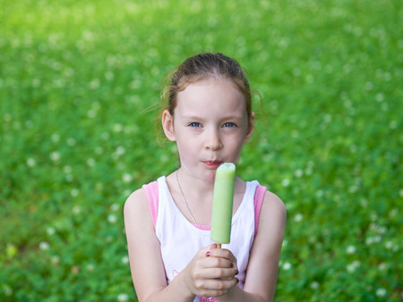 Adorable cute pretty little girl playing outdoors and eating ice cream in summer and eating ice cream. Happy childhood.