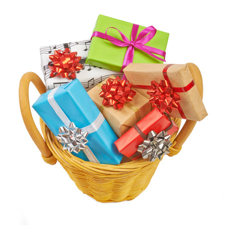 Many colored gift boxes in a basket isolated on white background photo
