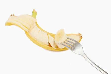 Banaan en rijp stuk prik met een vork op een witte
