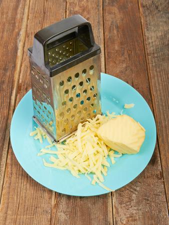 grated cheese: Queso rallado y rallador en un plato sobre la mesa
