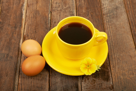 A cup of coffee, flower and eggs on a wooden table  photo