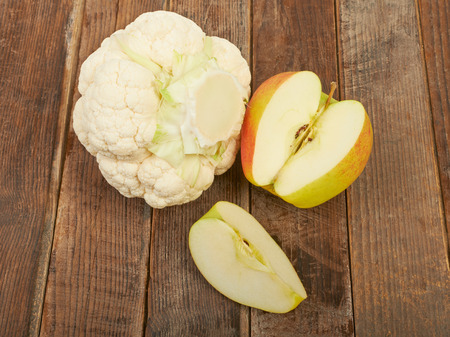 head of cauliflower: Cauliflower and apple on a wooden table