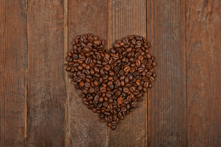 Coffee beans in the shape of a heart on a wooden background photo
