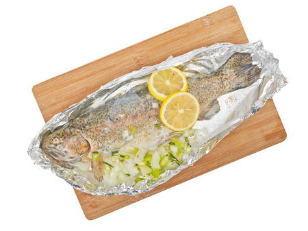 salmo: Fish fried trout in foil with lemon isolated on white background. Stock Photo