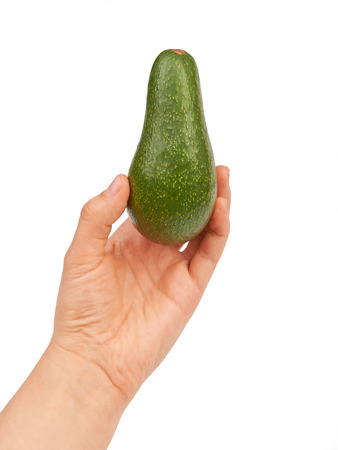 Green Avocado in hand isolated on white background photo