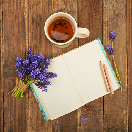 Notebook op een houten tafel achtergrond met een boeket van hyacint bloemen en een kopje thee