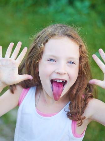 blonde yeux bleus: Portrait d'une petite fille mignonne qui montre la langue après avoir mangé des baies