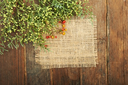 natural backgrounds: A piece of burlap and paper sheet on a wooden background with a sprig of arborvitae and red berries Stock Photo