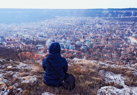 topsail: Young woman in a coat sitting on the ground. City view with mountains in Provadia in Bulgaria