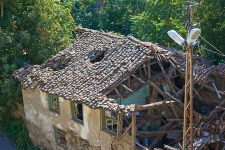 unsound: Old ruined house with a hole in the tile roof
