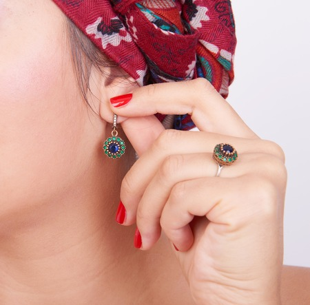 ear ring: Isolated ear with an earring and a hand with a ring near Stock Photo