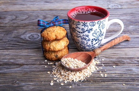 interleaved: Oatmeal cookies tasty breakfast, cereal in spoon and cacao drink on a wooden background Stock Photo