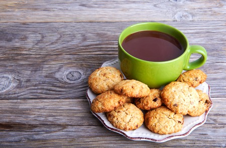 interleaved: Oatmeal cookies tasty breakfast and cacao drink in big green cap on a wooden background