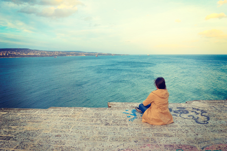 bulgaria girl: Hiker with backpack standing on top of a mountain and looks into the distance on blue sea in Bulgaria