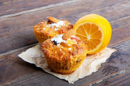 candied fruits: Carrot cupcakes with lemon and apple, nuts and candied fruits on wooden background