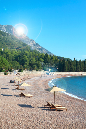 Sandy beach, sunny days, rainbow landscape and the Adriatic Sea in St. Stephen in Montenegro.