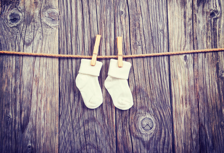 baby isolated: Baby goods hanging on the clothesline. Baby white socks on a clothespin on a wooden background Stock Photo