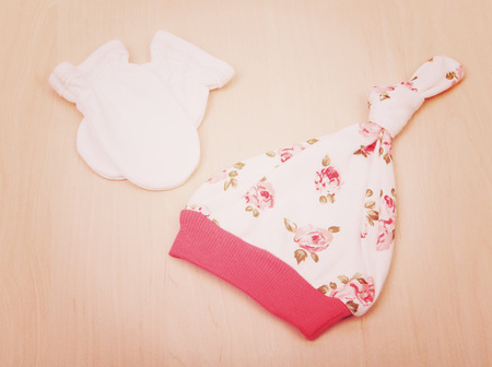 Baby goods. Childrens clothing, hat with flowers and white gloves on the background of the changing table. Baby clothes
