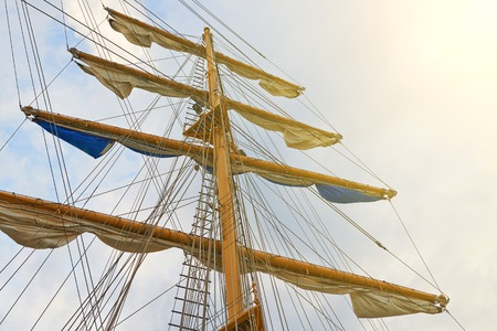 View of the masts of a sailing old ship and the sky illuminated by the suns rays Stockfoto