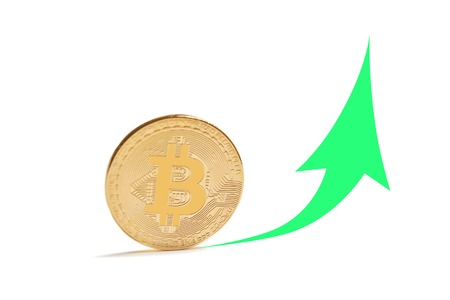 A golden bitcoin replica on white paper written with green graph up and down. Business and finance concept.