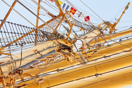 High wooden mast, old sailing ship with flags