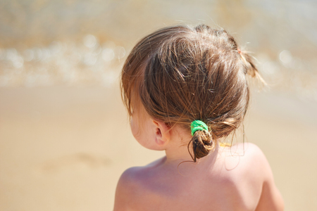 Little baby girl sitting on the beach and playing in waves. Stockfoto
