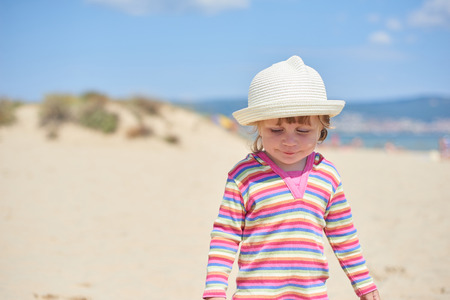 Little two year old girl with blue eyes in a bright wicker hat, standing on the beach near the sea