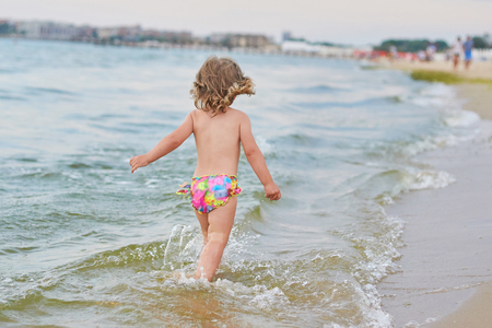 Happy child running and jumping in the waves during summer vacation on exotic tropical beach. Holiday on ocean coast for family with young children. Kids play at the sea. Little girl learning to swim. Stockfoto