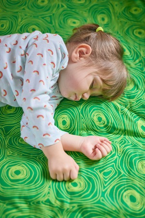 Two year old baby girl sleeping on bed.