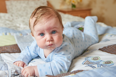 Cute baby of 6 months lying on the bed
