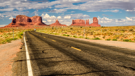 American road leading to Monument Valley at sunset Фото со стока