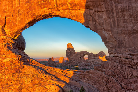 north window arch: Turret Arch seen through the North Window Arch at sunrise in Arches National Park near Moab, Utah Stock Photo