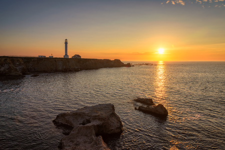 tybee island: Lighthouse Arena point searchlight beam near ocean at sunset Stock Photo