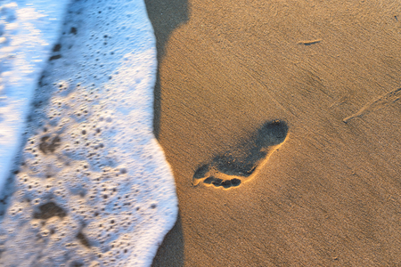 footsteps: Wave and footsteps at sunset in the sandy beach
