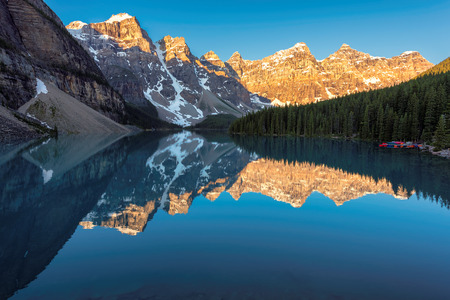 Beautiful sunrise at the Moraine lake with snow-covered peaks above it in Banff National Park of Canada Stock Photo