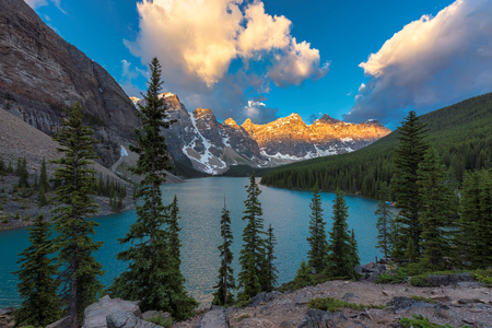 Beautiful sunrise under turquoise waters of the Moraine lake with snow-covered peaks above it in Canadian Rockies, Banff National Park of Canada