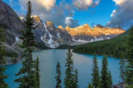 Beautiful sunrise under turquoise waters of the Moraine lake with snow-covered peaks above it in Banff National Park of Canada