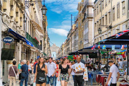 Happy tourists, with blur, on Rua Augusta Street in sunny day in Lisbon, Portugal. The Rua Augusta Arch and tourists cafes and restaurants in Lisbon. 新闻类图片