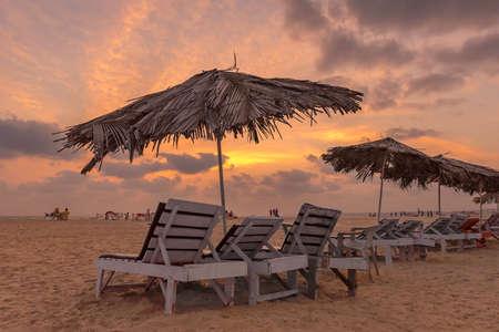 Goa tropical beach at sunset with deck chairs, GOA, Indian Ocean, India. 免版税图像