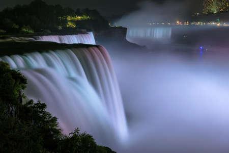 Niagara Falls lit at night by colorful lights. Niagara Falls, NY, USA.
