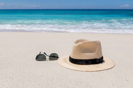 Beach accessories on sand beach for summer vacation, sunglasses and straw hat. Caribbean sea. 免版税图像