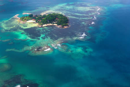 Island in the ocean around the blue water, Aerial view. A trip to an exotic Seychelles.